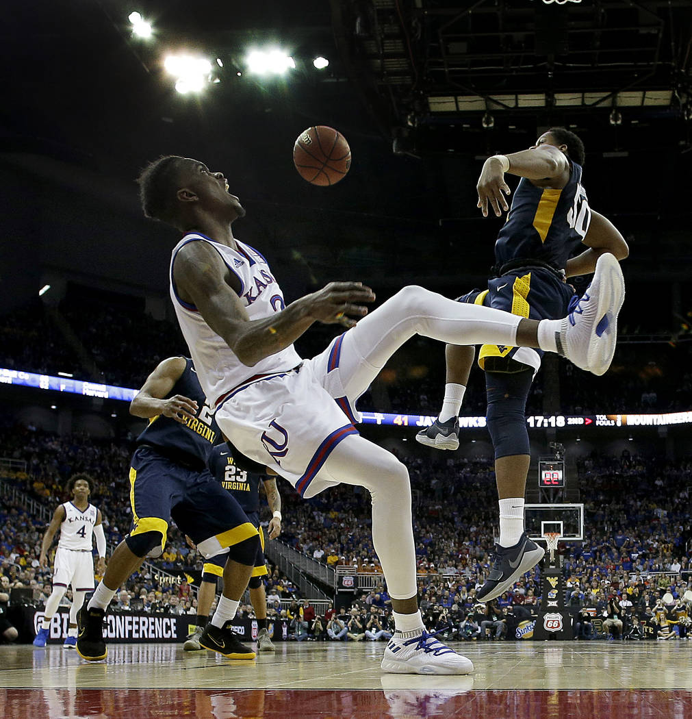 Kansas' Lagerald Vick falls to the floor after his shot was blocked by Sagaba Konate (50) during the second half of the NCAA college basketball championship game in the Big 12 men's tournament Sat ...