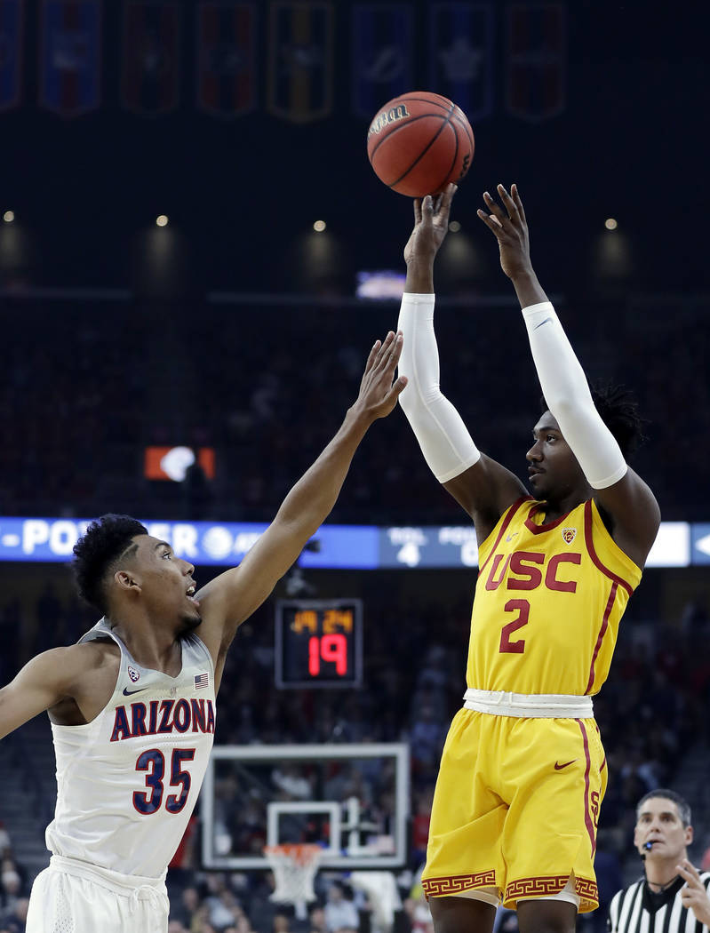 Arizona's Allonzo Trier, left, defends on a shot from Southern California's Jonah Mathews during the first half of an NCAA college basketball game in the Pac-12 men's tournament final Saturday, Ma ...