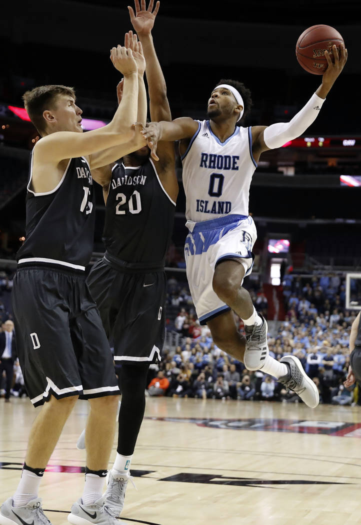 Rhode Island guard E.C. Matthews (0) shoots in front of Davidson forward Oskar Michelsen (15) and guard KiShawn Pritchett (20) during the first half of an NCAA college basketball championship game ...