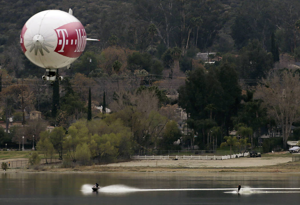 A blimp tows skiers on Lake Elsinore, Calif., on Tuesday, March 13, 2018.  The  blimp towed skier Kari McCollum for 6.9 miles for a new record, according to Philip Robertson, an adjudicator with G ...