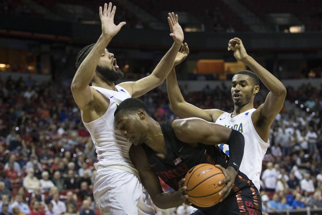 UNLV Rebels forward Brandon McCoy (44) is pressured by Nevada Wolf Pack forward Caleb Martin (10) and guard Josh Hall (33) in the second half of the Mountain West Conference men's basketball tourn ...
