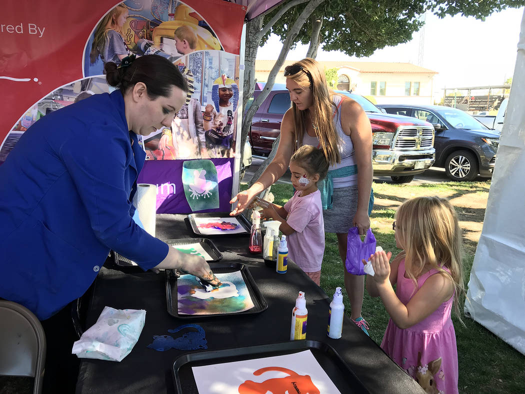 Angela Burnett, left, of Children's Discovery Museum in Las Vegas, helps Teagan Holmes, 6, of Las Vegas, far right, create a painting of her own as Sophia Soto, 5, gets a little assistance from he ...