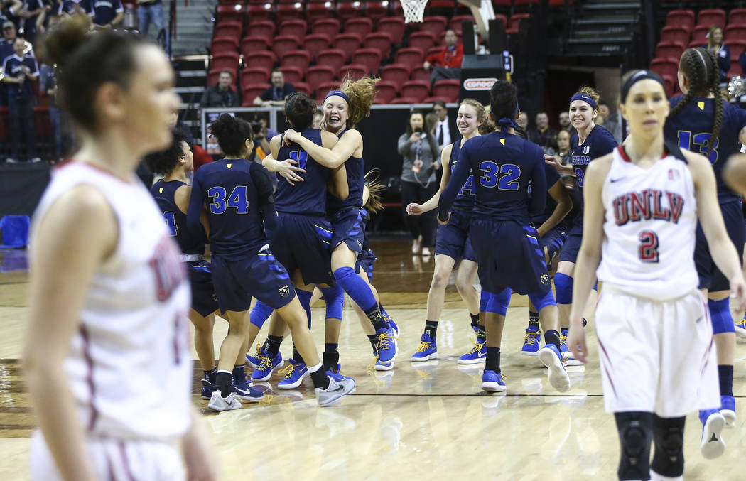 UNR Wolf Pack players celebrate their defeat over the UNLV Lady Rebels in double overtime in a Mountain West tournament quarterfinal game at the Thomas & Mack Center in Las Vegas on Tuesday, M ...