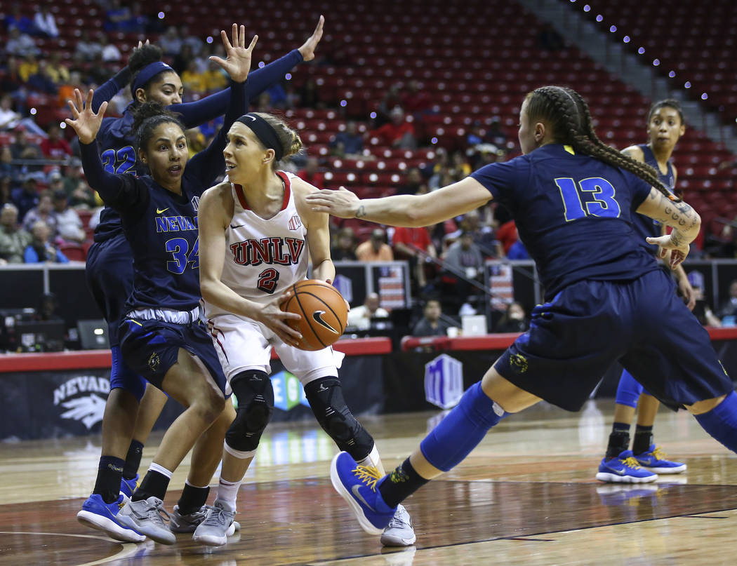 UNLV Lady Rebels guard Brooke Johnson (2) drives to the basket as UNR Wolf Pack guards Jade Redmon (34) and T Moe (13) defend during overtime in a basketball game in the Mountain West tournament q ...