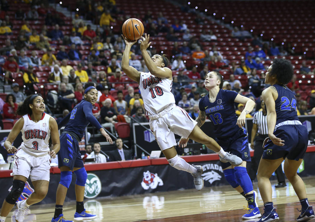 UNLV Lady Rebels guard Nikki Wheatley (10) sends up a shot past UNR Wolf Pack guard T Moe (13) during the second half of a basketball game in the Mountain West tournament quarterfinals at the Thom ...