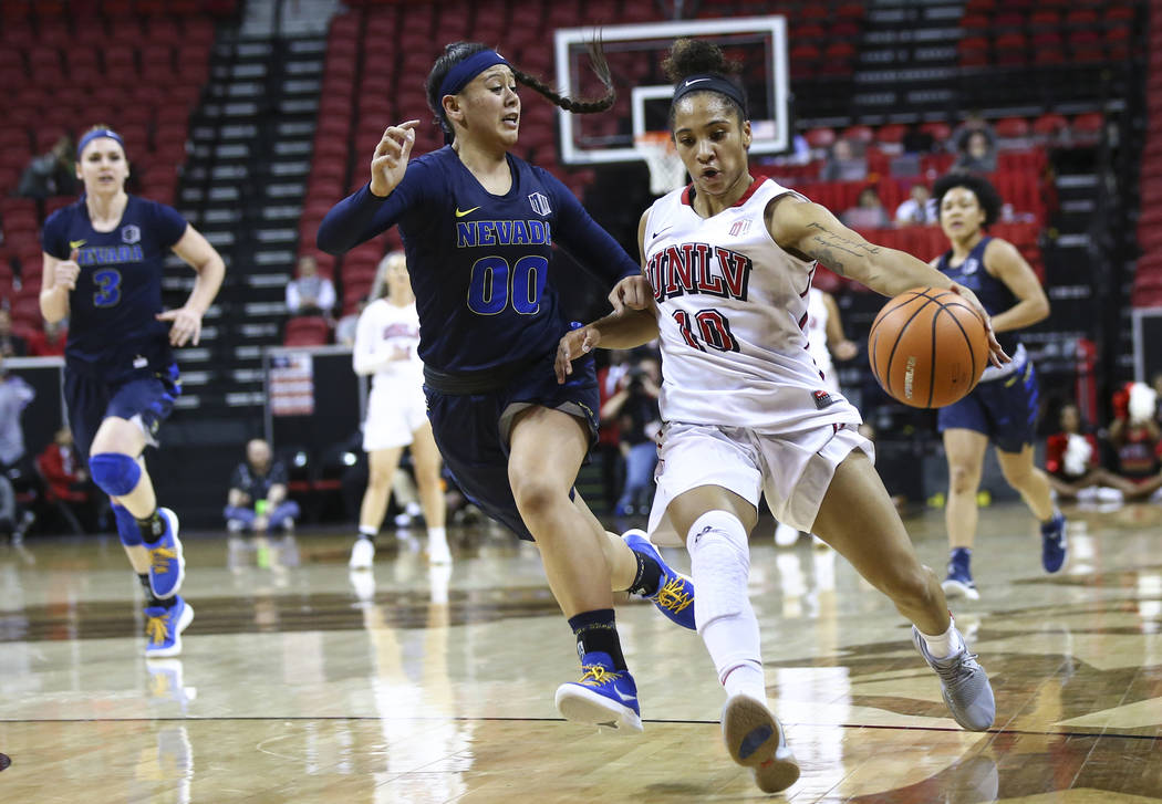 UNLV Lady Rebels guard Nikki Wheatley (10) drives against UNR Wolf Pack guard Janelle Sumilong (00) during the first half of a basketball game in the Mountain West tournament quarterfinals at the  ...