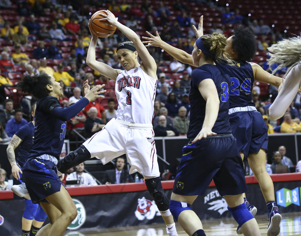 UNLV Lady Rebels guard Brooke Johnson (2) gets a rebound between UNR Wolf Pack guard Jade Redmon, left, and forward Teige Zeller (3) during the second half of a basketball game in the Mountain Wes ...