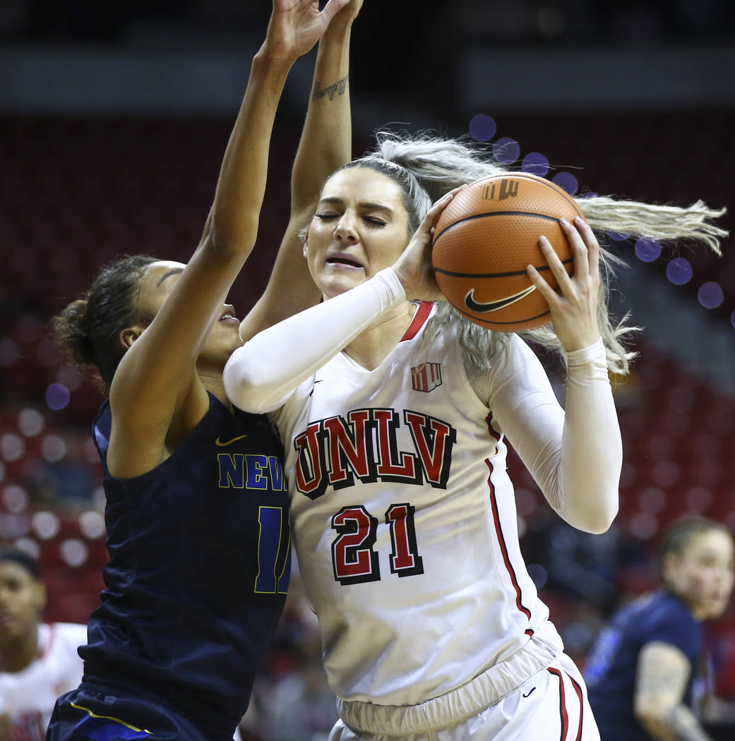 UNLV Lady Rebels forward/center Katie Powell (21) drives as UNR Wolf Pack forward Terae Briggs (11) defends during overtime in a basketball game in the Mountain West tournament quarterfinals at th ...