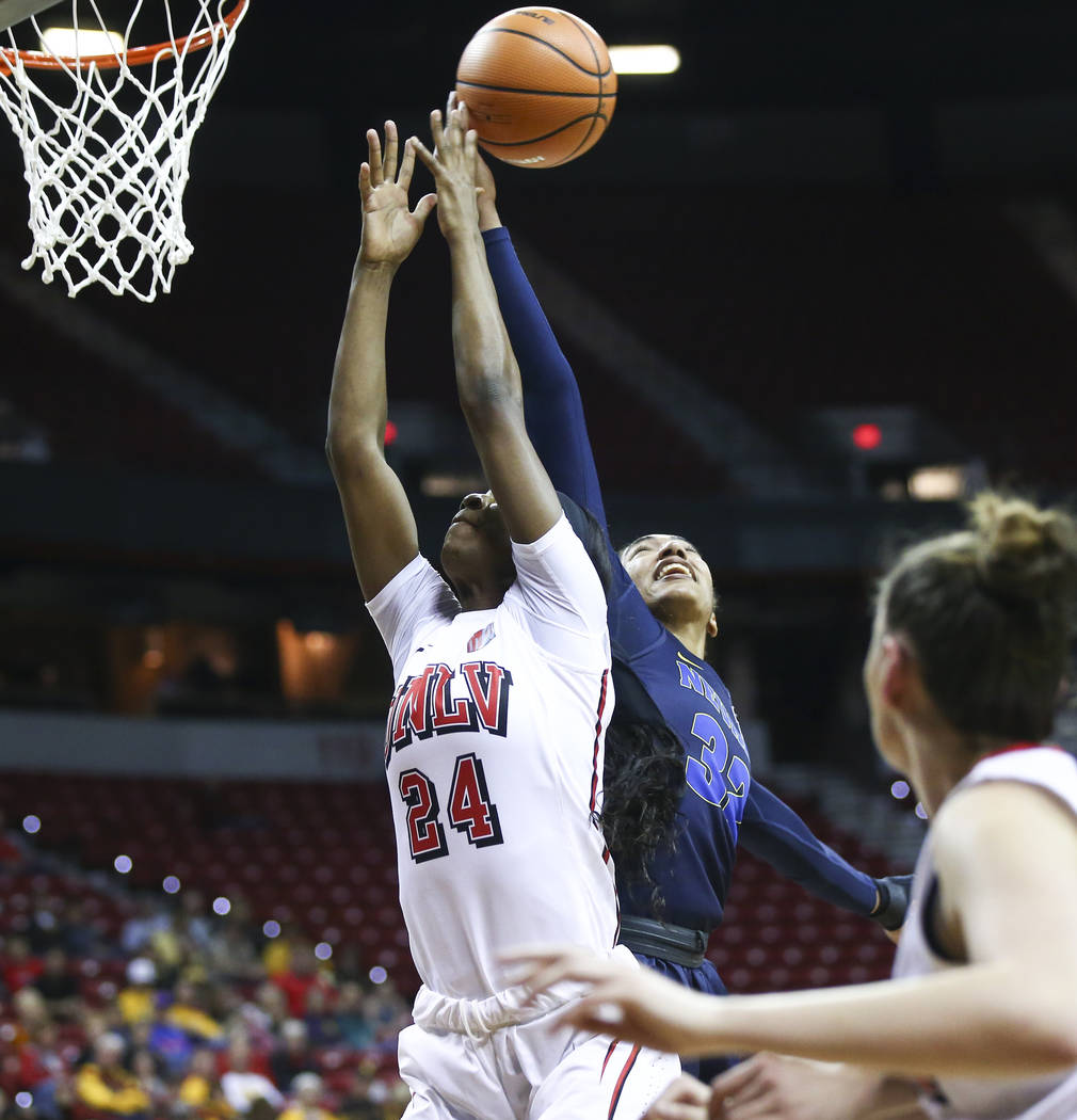 UNR Wolf Pack forward AJ Cephas (32) gets a rebound over UNLV Lady Rebels center Rodjanae Wade (24) during the first half of a basketball game in the Mountain West tournament quarterfinals at the  ...