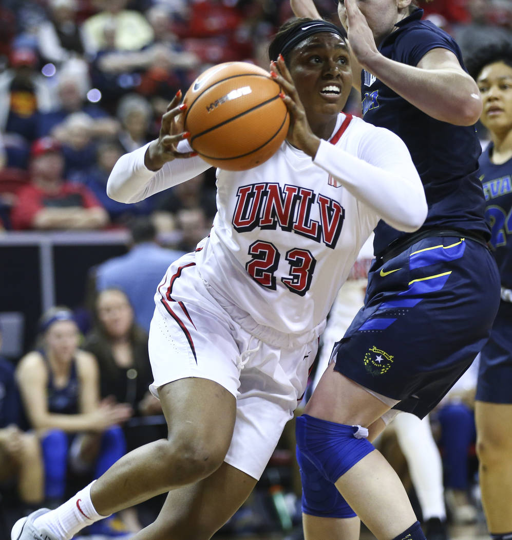 UNLV Lady Rebels forward Jordyn Bell (23) drives to the basket past UNR Wolf Pack forward Teige Zeller (3) during the first half of a basketball game in the Mountain West tournament quarterfinals  ...