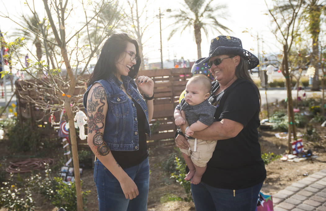 Oct. 1 shooting survivor Sue Ann Cornwell, right, holds infant Xander Finch whose mother Miriam Lujan, left, was rescued by Cornwell at the Route 91 festival, while visiting the Community Healing  ...