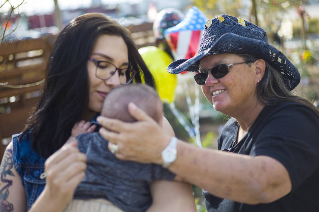 Oct. 1 shooting survivor Sue Ann Cornwell, right, talks with infant Xander Finch whose mother Miriam Lujan, left, was rescued by Cornwell at the Route 91 festival. They reunited while visiting the ...