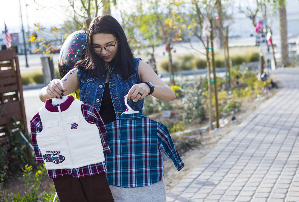 Oct. 1 shooting survivor Miriam Lujan looks at gifts for her son Xander Finch given to her by survivor Sue Ann Cornwell, who helped rescue Lujan at the Route 91 festival, while visiting the Commun ...