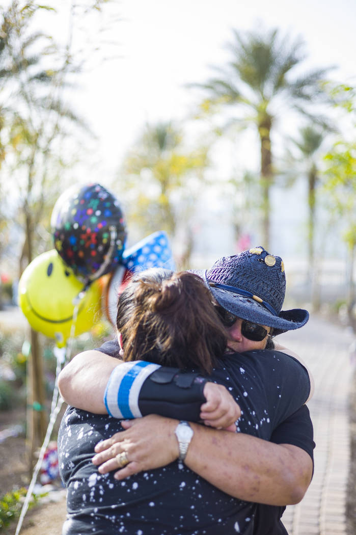 Oct. 1 shooting survivor Sue Ann Cornwell, right, hugs fellow survivor Cynthia Velez at the Community Healing Garden in downtown Las Vegas on Friday, March 9, 2018. Cornwell and Lujan were visitin ...