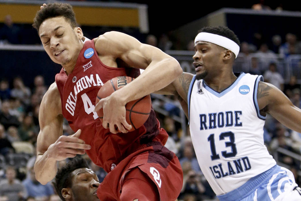 Oklahoma's Jamuni McNeace (4) grabs a rebound in front of Rhode Island's Stanford Robinson (13) during the first half in the first round of the NCAA men's college basketball tournament, Thursday,  ...