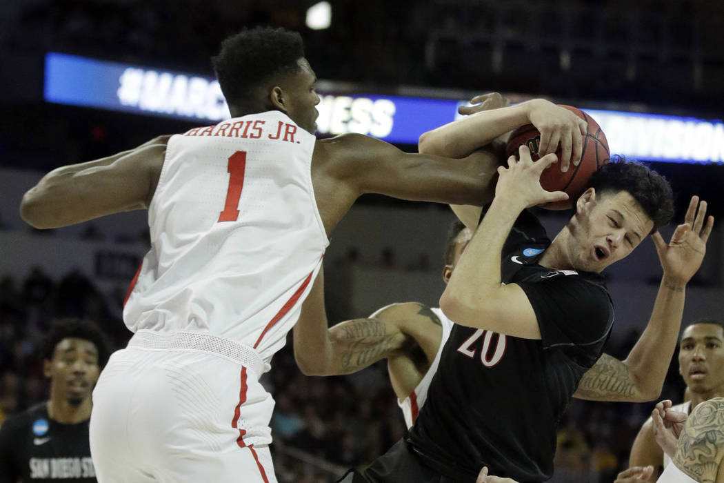 San Diego State guard Jordan Schakel (20) is fouled by Houston center Chris Harris Jr. (1) during the first half of an NCAA college basketball tournament first-round game, Thursday, March 15, 2018 ...
