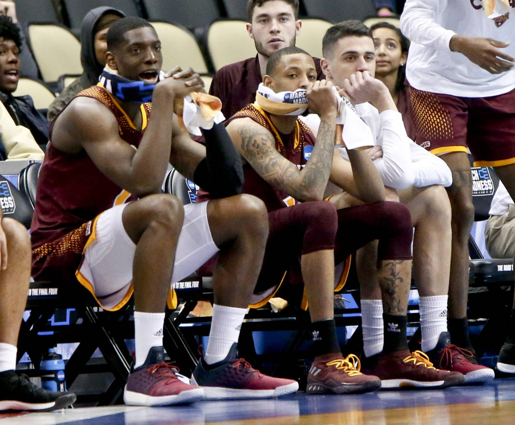 Iona's TK Edogi, left. and Zach Lewis, center, watch with teammates as their team is losing to Duke in the second half of an NCAA men's college basketball tournament first-round game, Thursday, Ma ...