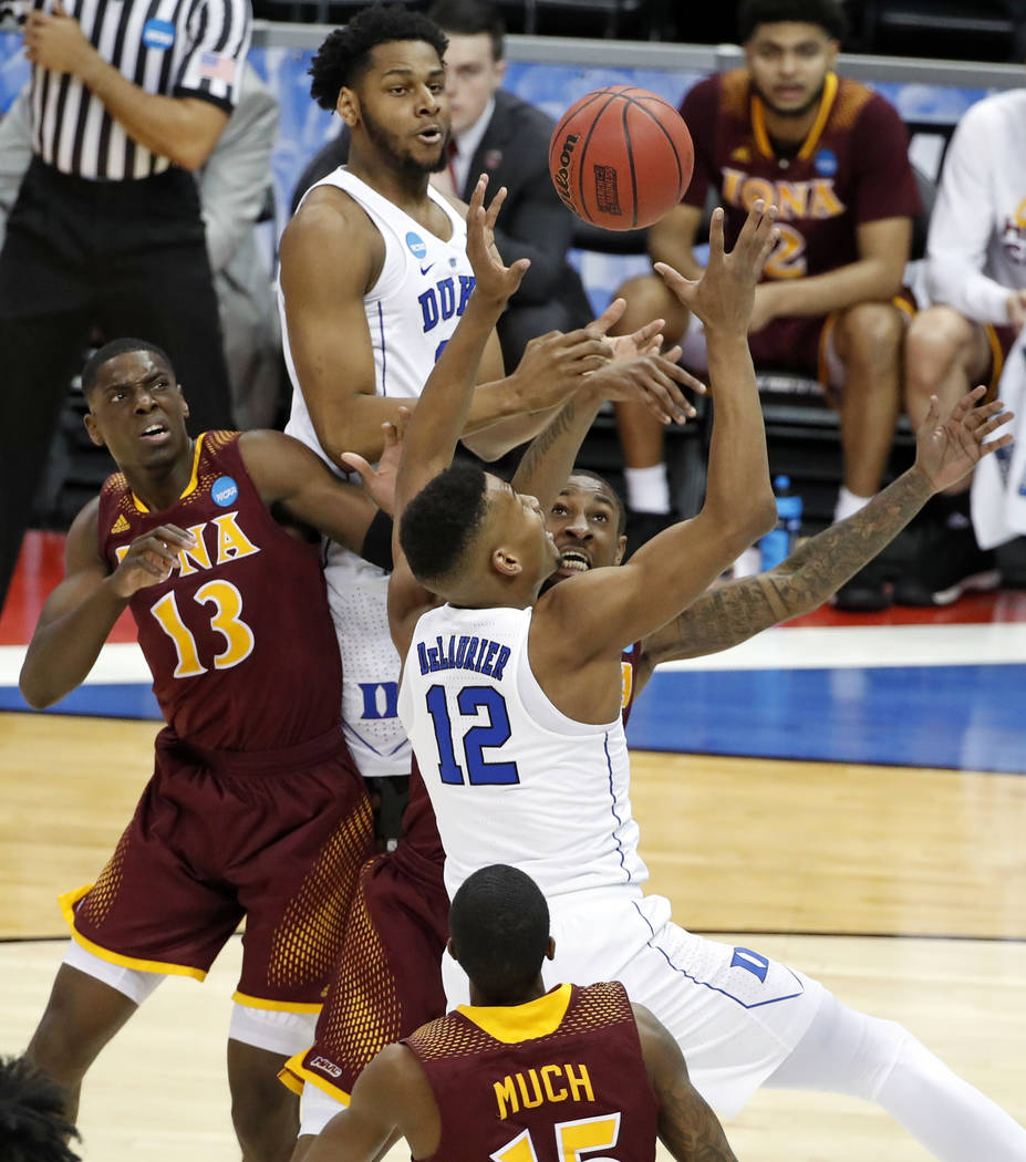 Duke's Javin DeLaurier (12) battles for a rebound with Iona's Rickey McGill, rear, and TK Edogi (13) during the first half of an NCAA men's college basketball tournament first-round game, in Pitts ...