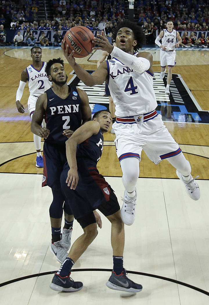 Kansas guard Devonte' Graham (4) puts up a shot during the second half of an NCAA college basketball tournament first-round game against Pennsylvania Thursday, March 15, 2018, in Wichita, Kan. Kan ...