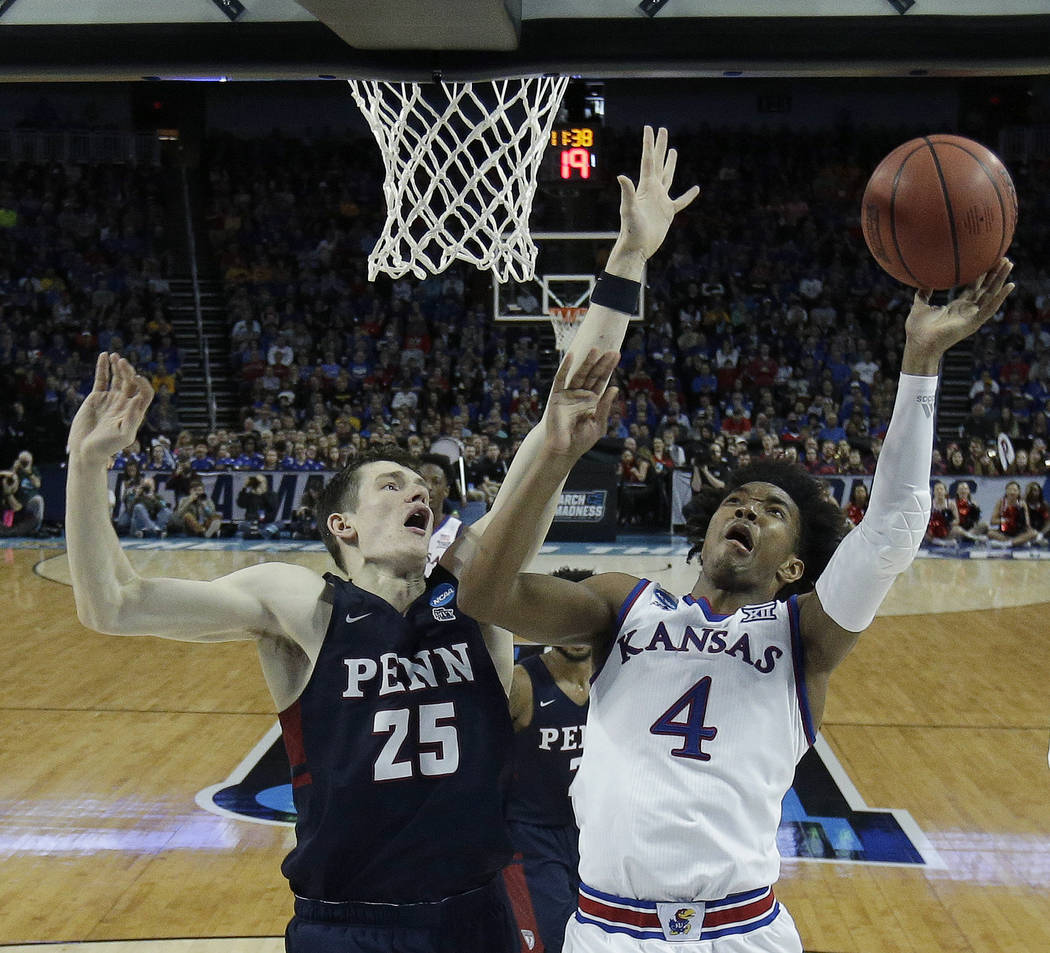 Kansas guard Devonte' Graham (4) is pressured by Pennsylvania forward AJ Brodeur (25) as he shoots during the second half of an NCAA college basketball tournament first-round game Thursday, March  ...
