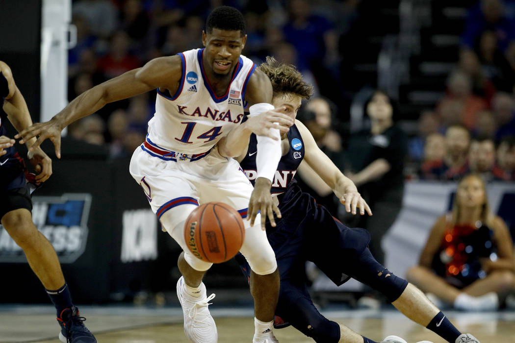 Kansas guard Malik Newman (14) and Pennsylvania guard Caleb Wood (10) chase a loose ball during the second half of an NCAA college basketball tournament first-round game Thursday, March 15, 2018,  ...