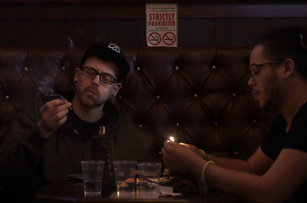 In this March 1, 2018 photo, Rick Thompson, patrons smoke marijuana while sitting in a booth in the smoking lounge at Barbary Coast Dispensary in San Francisco. San Francisco plans to issue more p ...