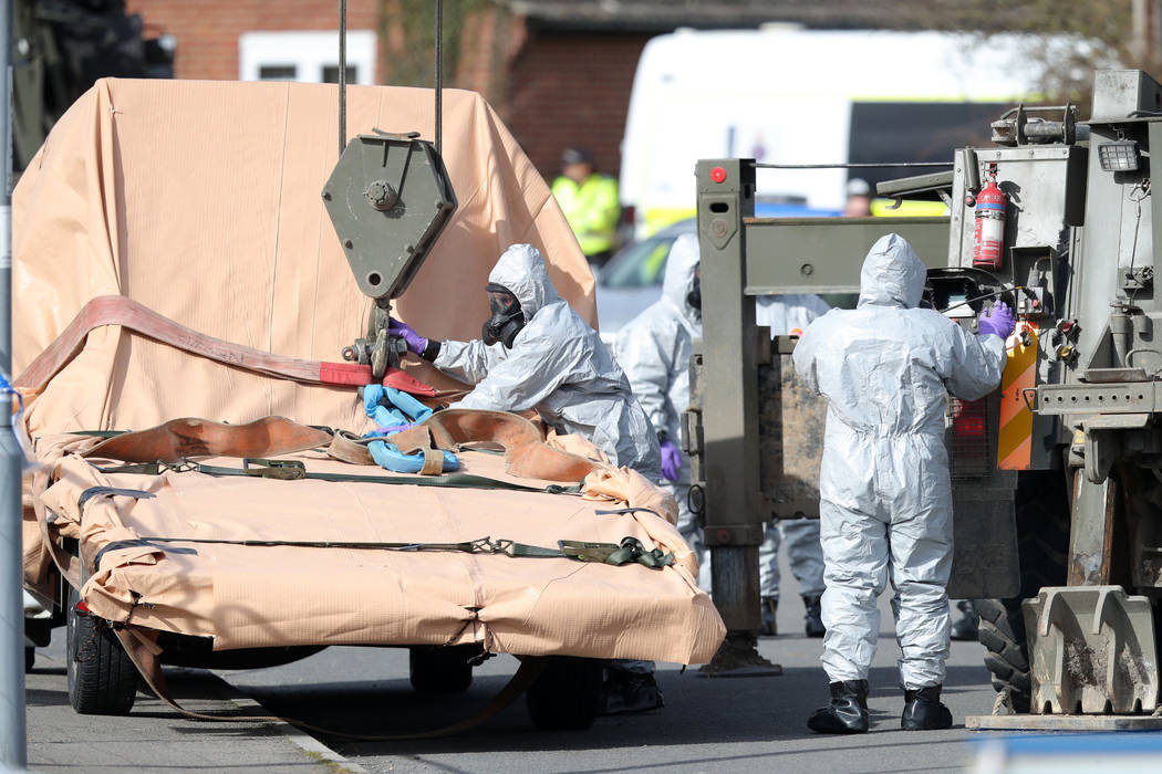 Soldiers wearing protective clothing prepare to lift a tow truck in Hyde Road, Gillingham, Dorset, England as the investigation into the suspected nerve agent attack on Russian double agent Sergei ...