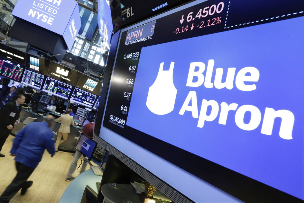 FILE- In this July 18, 2017, file photo, the Blue Apron logo appears above a trading post on the floor of the New York Stock Exchange. Blue Apron, which ships boxes of raw food to subscriber&#x201 ...