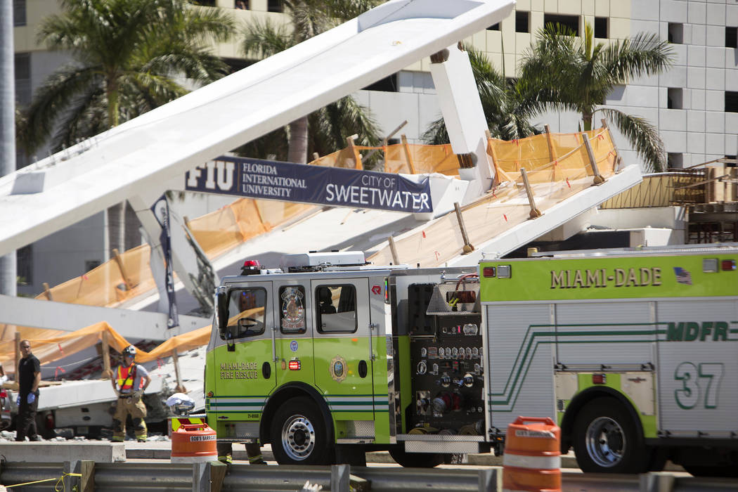 Emergency personnel responds to a collapsed pedestrian bridge at Florida International University on Thursday, March 15, 2018 in the Miami area.  The  brand-new pedestrian bridge collapsed onto a  ...