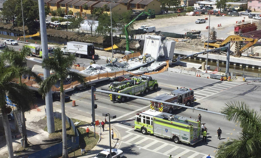 Emergency personnel responds to a collapsed pedestrian bridge connecting Florida International University on Thursday, March 15, 2018 in the Miami area.  The  brand-new pedestrian bridge collapsed ...