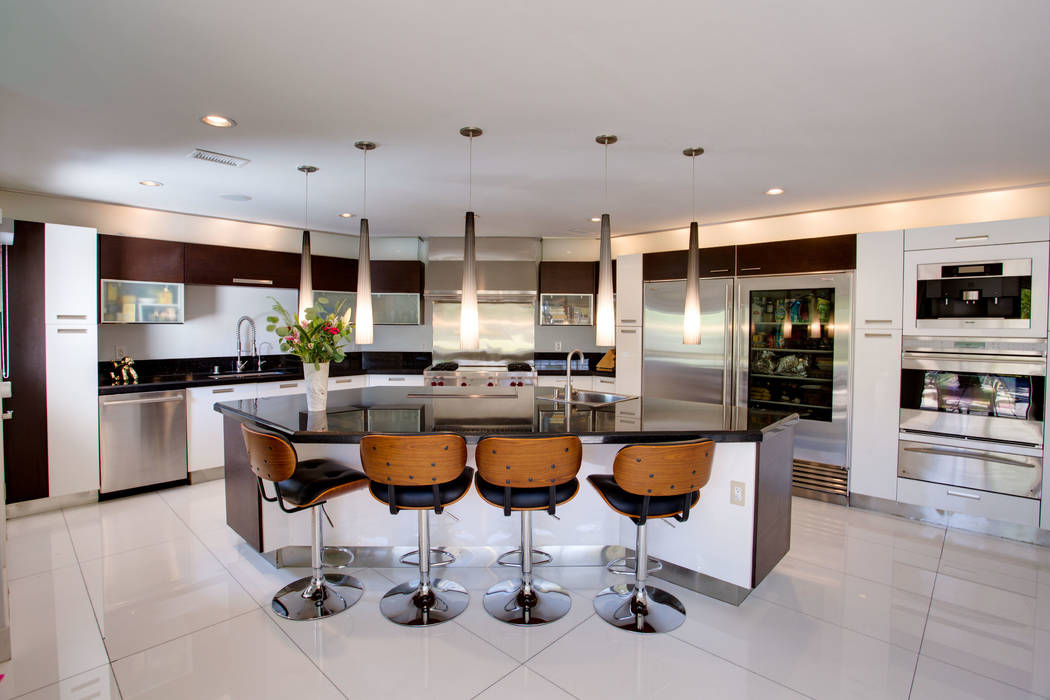 The kitchen is sleek and modern with some retro overtones and has high-end lighting treatments.  (Berkshire Hathaway HomeServices)