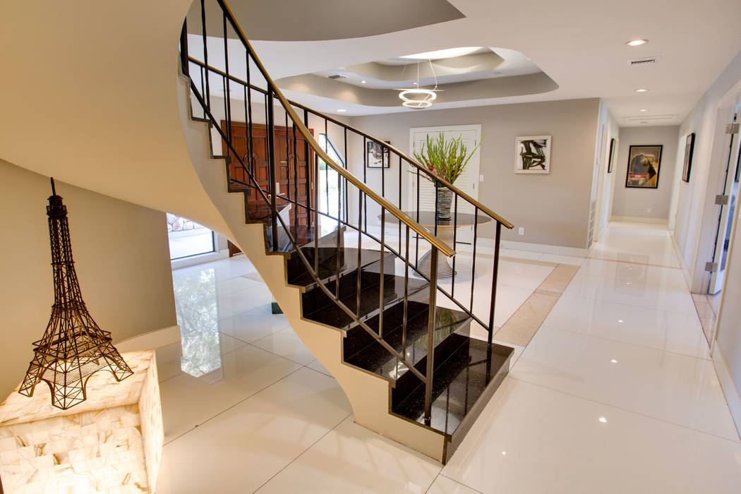Large slabs of expensive, white porcelain flooring is laid throughout the home. This staircase is near the foyer. (Berkshire Hathaway HomeServices)