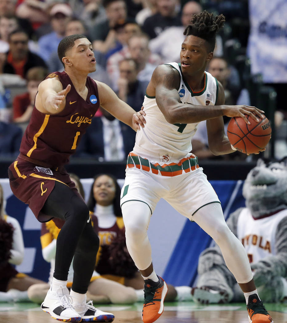 Loyola-Chicago guard Lucas Williamson, left, defends as Miami guard Lonnie Walker IV, right, prepares to make a pass in the first half of a first-round game at the NCAA college basketball tourname ...