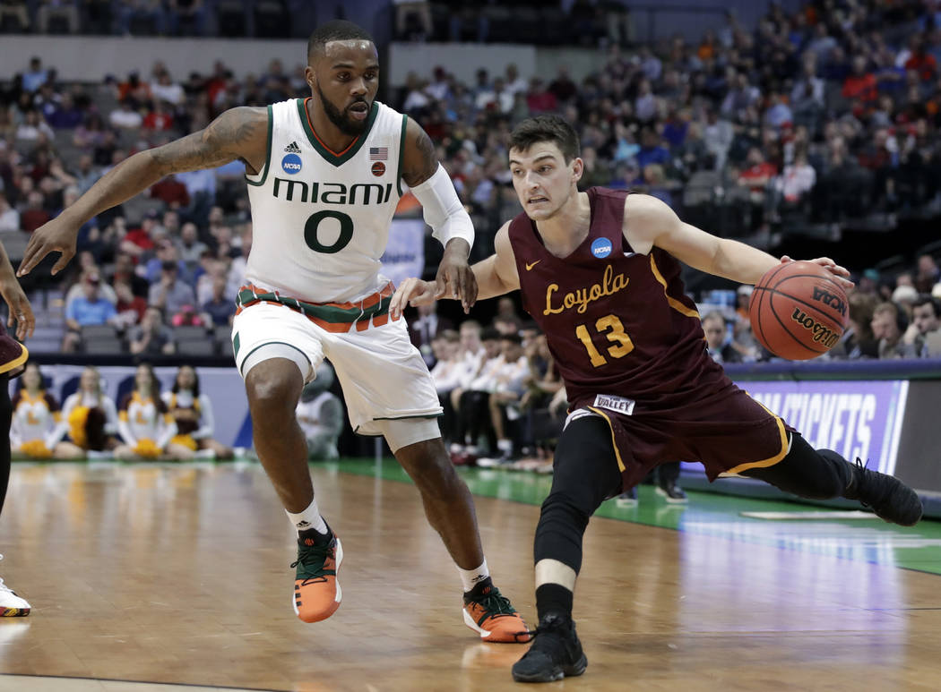 Miami guard Ja'Quan Newton (0) defends against a drive to the basket by Loyola-Chicago guard Clayton Custer (13) in the first half of a first-round game of the NCAA college basketball tournament i ...