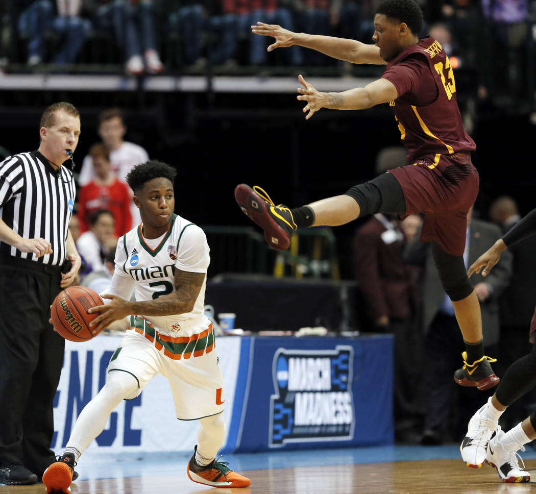Miami guard Chris Lykes, left, prepares to pass as Loyola-Chicago guard Cameron Satterwhite, right, defends in the first half of a first-round game at the NCAA college basketball tournament in Dal ...