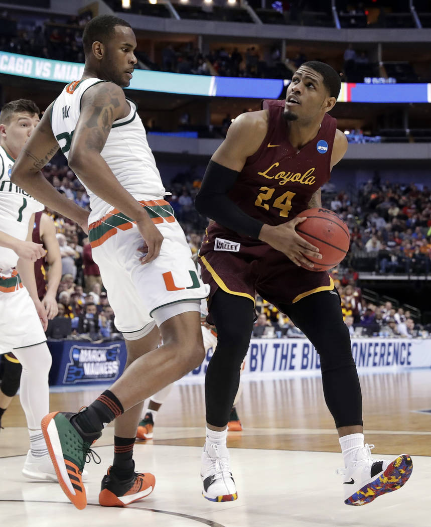 Miami forward Dewan Huell (20) defends as Loyola-Chicago forward Aundre Jackson (24) works for a shot attempt in the first half of a first-round game at the NCAA college basketball tournament in D ...