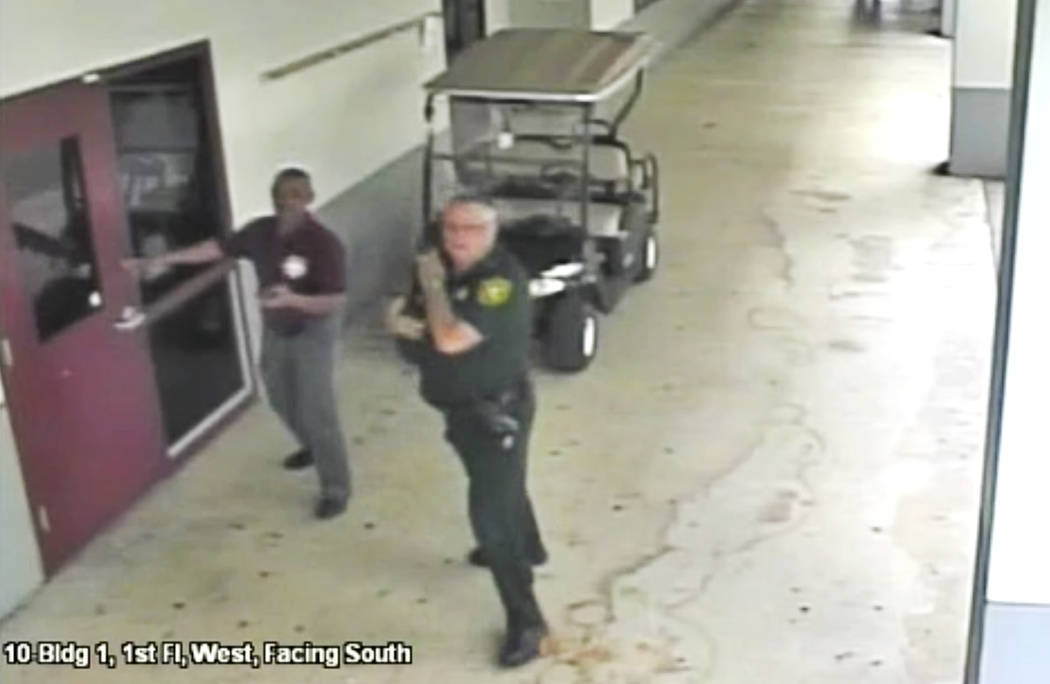 This Feb. 14, 2018 frame from security video provided by the Broward County Sheriff's Office shows deputy Scot Peterson, right, outside Marjory Stoneman Douglas High School in Parkland, Fla. The v ...