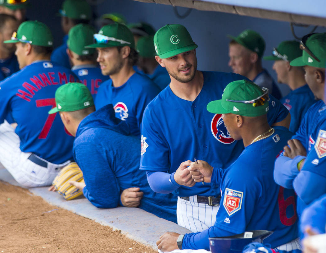 Chicago Cubs third baseman Kris Bryant, center, fist-bumps assistant bullpen coach Franklin Font before playing the Cleveland Indians in the annual Big League Weekend baseball game at Cashman Fiel ...