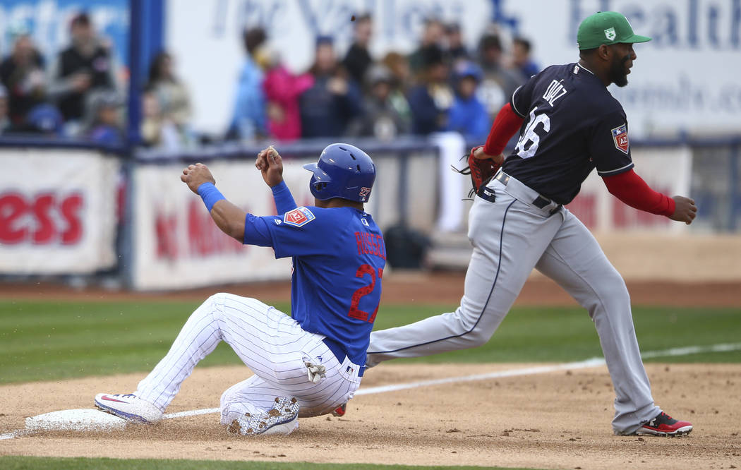 Chicago Cubs shortstop Addison Russell (27) makes it to third base against Cleveland Indians third baseman Yandy Diaz (36) during the annual Big League Weekend baseball game at Cashman Field in La ...
