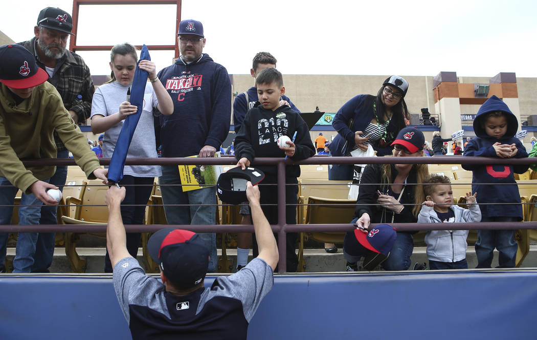 Cleveland Indians relief pitcher Cameron Hill, left, signs autographs for fans before the start of the annual Big League Weekend baseball game at Cashman Field in Las Vegas on Saturday, March 17,  ...