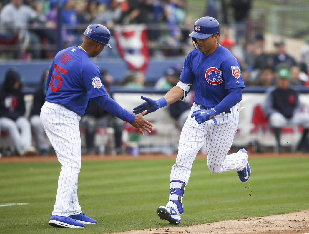 Chicago Cubs' Jacob Hannemann high-fives assistant bullpen coach Franklin Font (65) after rounding third on a home run against the Cleveland Indians during an exhibition baseball game in Las Vegas ...