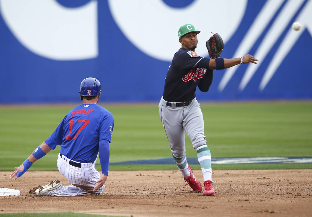 Cleveland Indians shortstop Francisco Lindor throws to first base after putting out Chicago Cubs' Kris Bryant (17) during an exhibition baseball game in Las Vegas on Saturday, March 17, 2018. (Cha ...