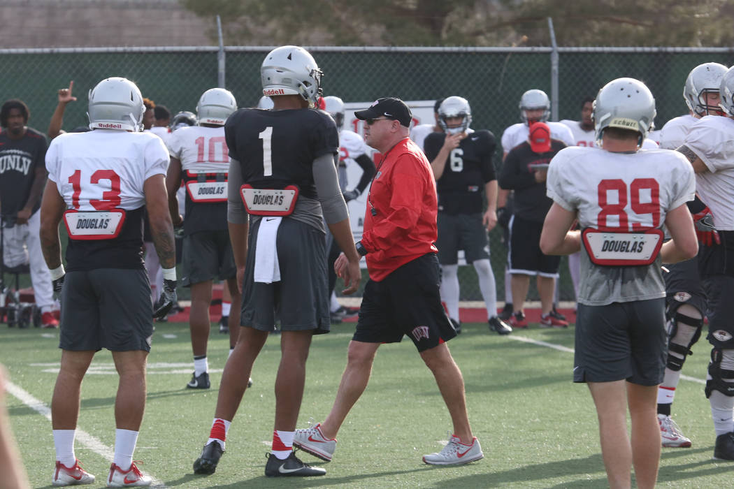 UNLV Rebels head coach Tony Sanchez, center, talks to his players as quarterback Armani Rogers (1) looks on during team practice on Tuesday, March 13, 2018, in Las Vegas. Bizuayehu Tesfaye/Las Veg ...