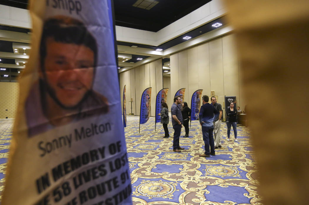 People attend a presentation of flags bearing the names and photos of the victims of the Oct. 1 shooting at the Westgate in Las Vegas on Thursday, March 15, 2018. The flags are slated to be used i ...