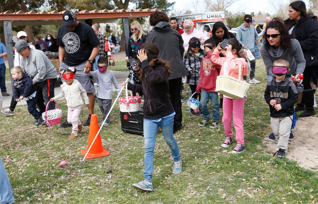 Children with visual impairments and their families look for beeping eggs during the Beepin' Egg Hunt at Sunset Park in Las Vegas, Saturday, March 24, 2018. Nevada Blind Children's Foundation host ...