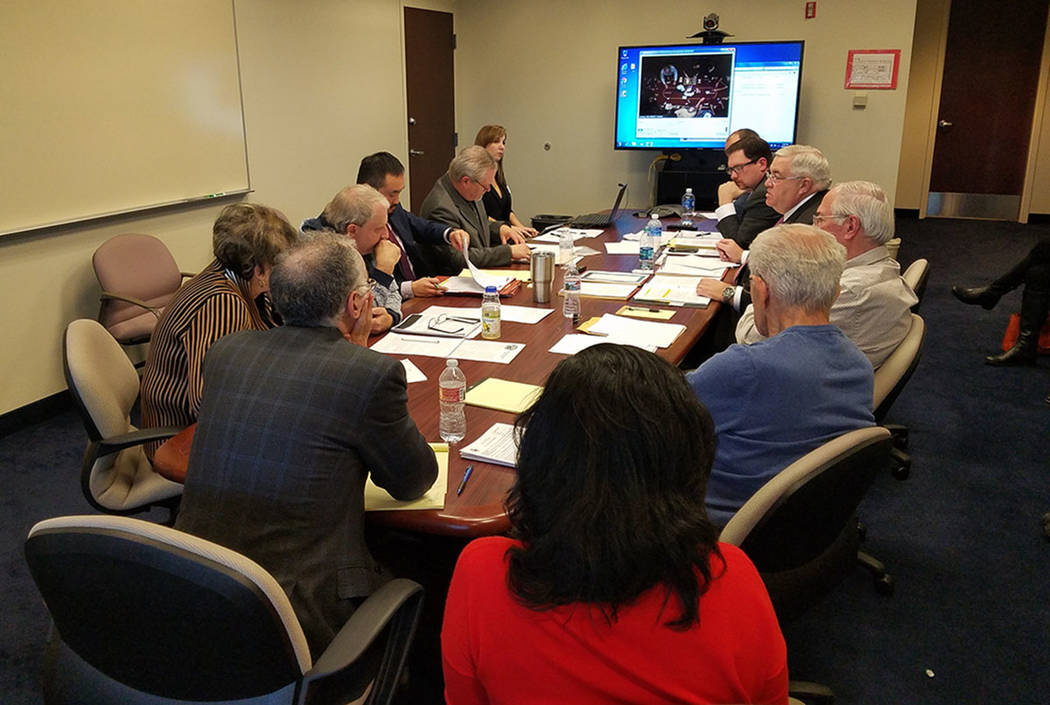 Poker players, Station Casinos' poker room officials and state Gaming Control Board administrators gather around a table in a conference room at the Gaming Control Board offices at the Sawyer Buil ...