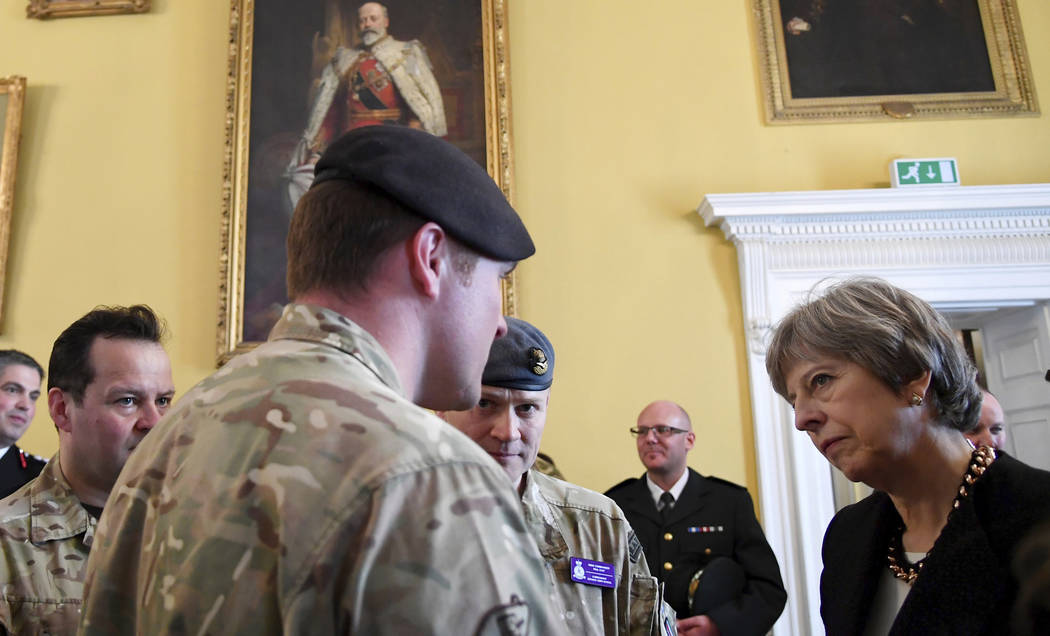 Britain's Prime Minister Theresa May speaks to members of military as she visits Salisbury southwest England, Thursday March 15, 2018 . may was in Salisbury view the area of Sunday's suspected ner ...