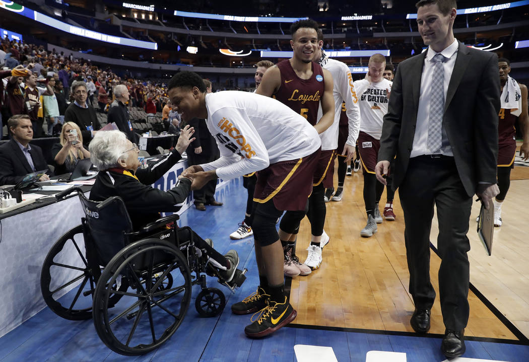 Sister Jean Dolores Schmidt, left, greets the Loyola-Chicago basketball team as they walk off the court after their win over Miami in a first-round game at the NCAA college basketball tournament i ...