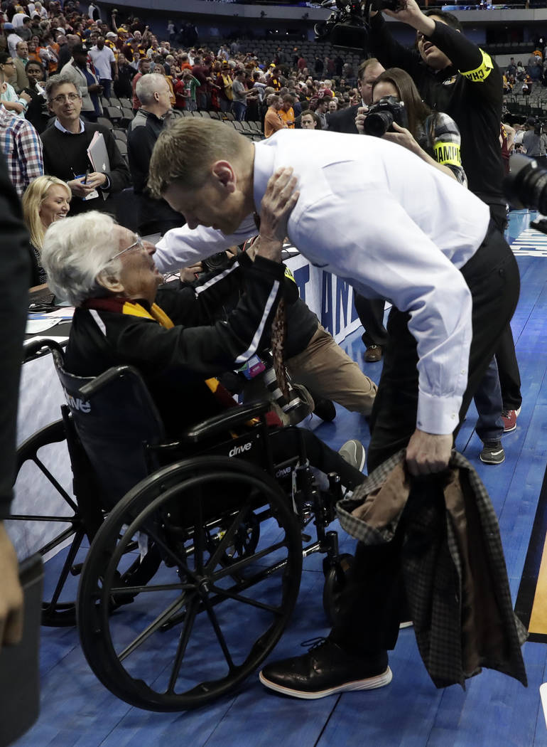Sister Jean Dolores Schmidt, left, greets Loyola-Chicago coach Porter Moser as he walks off the court after the team's first-round game against Miami at the NCAA men's college basketball tournamen ...
