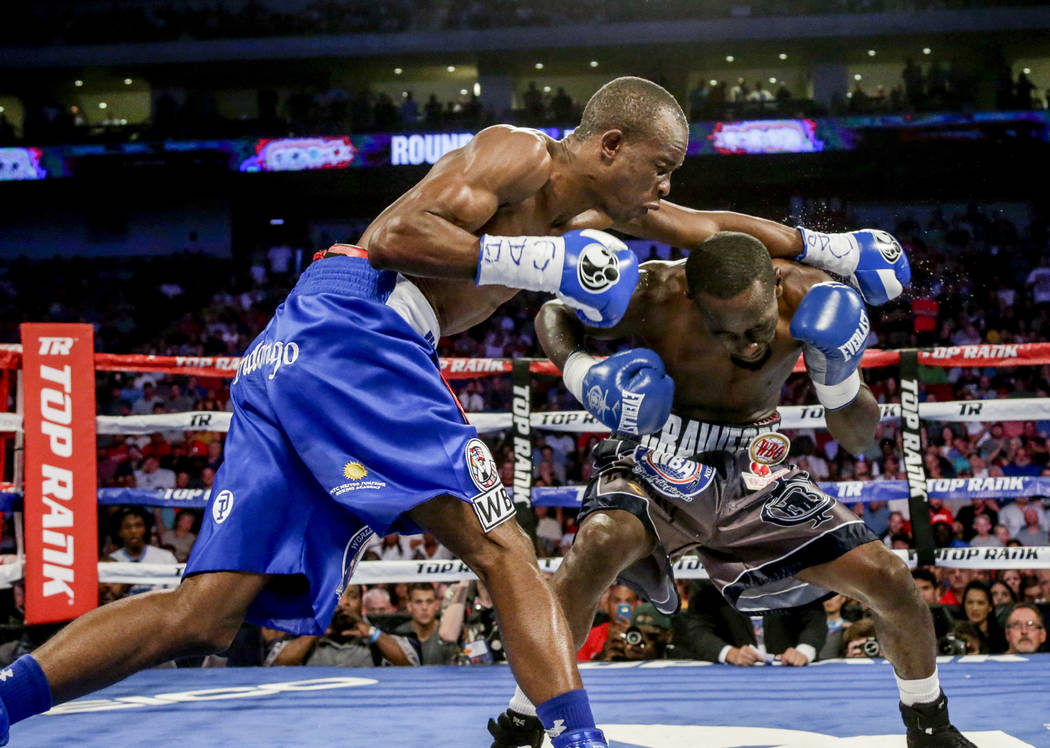 """Terence """"Bud"""" Crawford, right, ducks under a punch by Julius Indongo in a junior welterweight world title unification bout in Lincoln, Neb., Saturday, Aug. 19, 2017. Crawford won by knoc ..."""